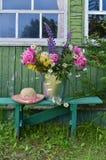 Fondo del verano con las flores por la ventana vieja Imágenes de archivo libres de regalías