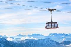 Fondo del viaje de los deportes de invierno con el teleférico, picos de montaña Foto de archivo libre de regalías