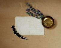 Fondo del vintage con la postal vieja, la tabaquera, el ramo de lavanda y las plumas fotografía de archivo