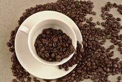 Fondo del vintage de la sepia de la taza de café y de los granos de café fotos de archivo