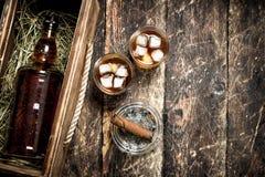 Fondo del whisky Una botella de whisky en una caja vieja con vidrios y un cigarro Imagen de archivo libre de regalías