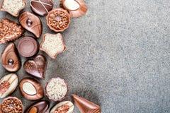 Fondo delicioso clasificado de las almendras garapiñadas del chocolate en la textura gris, lugar para el texto, fotografía del pr foto de archivo libre de regalías