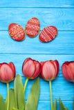 Fondo delicioso de las galletas de Pascua con los tulipanes Imágenes de archivo libres de regalías