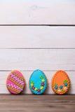 Fondo delicioso de las galletas de Pascua Galletas coloridas de Pascua por todo el fondo de madera blanco Huevos con diferente Imagen de archivo libre de regalías