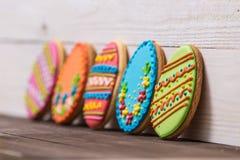 Fondo delicioso de las galletas de Pascua Galletas coloridas de Pascua por todo el fondo de madera blanco Huevos con diferente Foto de archivo