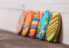 Fondo delicioso de las galletas de Pascua Galletas coloridas de Pascua por todo el fondo de madera blanco Huevos con diferente Foto de archivo libre de regalías