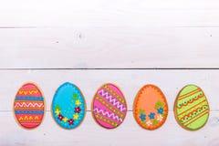 Fondo delicioso de las galletas de Pascua Galletas coloridas de Pascua por todo el fondo de madera blanco Huevos con diferente Imagenes de archivo