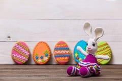 Fondo delicioso de las galletas de Pascua Galletas y conejito coloridos de Pascua por todo el fondo de madera blanco Huevos con Imagenes de archivo