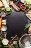 Fondo dell'alimento con gli ingredienti ed il vaso organici freschi per la minestra di verdure o il brodo che cucina, vista super Immagini Stock