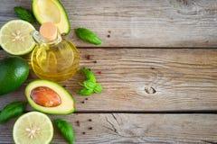 Fondo dell'alimento con l'avocado, la calce, l'olio d'oliva ed il basilico su vecchio w Immagine Stock