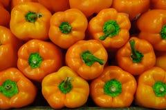 Fondo dell'alimento - peperoni dolci arancio con i gambi verdi che formano un'esposizione simmetrica fotografia stock