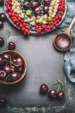 Fondo dell'alimento per le ricette con le varie bacche, cucinante cucchiaio, le ciotole e tovagliolo, vista superiore Fotografie Stock