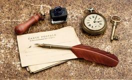 Fondo dell'annata con le vecchie cartoline e penna della piuma Fotografia Stock