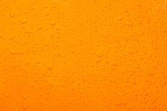 Fondo dell'arancia di colore della goccia di acqua Immagine Stock