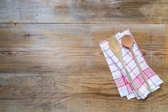 Fondo dell'asciugamano di cucina con i cucchiai di legno Fotografie Stock Libere da Diritti