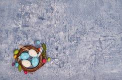 fondo dell'aster Uova di Pasqua decorative nella piccola carta di festa del nido con lo spazio della copia Fotografie Stock Libere da Diritti