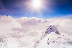 Fondo dell'estratto del bokeh del fascio del sole delle nuvole del vento delle montagne del cielo di inverno estremamente altamen Immagini Stock