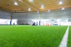 Fondo dell'estratto della sfuocatura del campo di formazione di calcio dell'interno Fotografie Stock Libere da Diritti