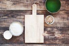 Fondo della cucina con il tagliere di legno anziano vuoto e gli ingredienti organici immagini stock