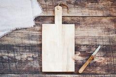 Fondo della cucina con il vecchi tagliere e coltello di legno vuoti fotografia stock libera da diritti