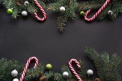 Fondo della decorazione del nuovo anno o di Natale: l'abete si ramifica, palle variopinte, caramella su fondo nero con lo spazio  Fotografia Stock