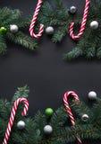 Fondo della decorazione del nuovo anno o di Natale Rami di albero dell'abete, abete rosso, caramella, palle variopinte su fondo n Fotografia Stock