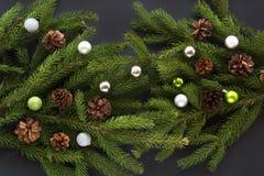 Fondo della decorazione di Natale: il cono, abete si ramifica, palle di vetro variopinte su fondo nero Vista superiore Immagine Stock Libera da Diritti