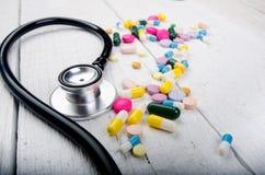 Fondo della farmacia su una tavola bianca Stetoscopio su un fondo di legno bianco Copi lo spazio per un testo Compresse su un bac Fotografie Stock Libere da Diritti