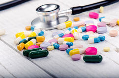 Fondo della farmacia su una tavola bianca Stetoscopio su un fondo di legno bianco Copi lo spazio per un testo Compresse su un bac Fotografie Stock