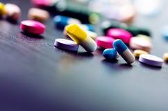 Fondo della farmacia su una tavola nera Compresse su un fondo nero Pillole Medicina e sano Chiuda in su delle capsule Differend Fotografia Stock