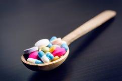 Fondo della farmacia su una tavola nera con nastro adesivo di misurazione Compresse su un cucchiaio di legno Pillole Medicina e s Fotografie Stock Libere da Diritti