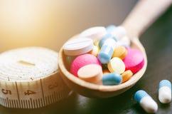 Fondo della farmacia su una tavola nera con nastro adesivo di misurazione Compresse su un cucchiaio di legno Pillole Medicina e s Immagini Stock Libere da Diritti