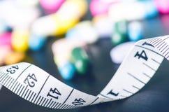 Fondo della farmacia su una tavola nera con nastro adesivo di misurazione Compresse su un fondo nero Pillole Medicina e sano Chiu Fotografia Stock
