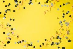 Fondo della festa di compleanno Tavola gialla con i coriandoli ed il nastro Posto per testo fotografia stock libera da diritti