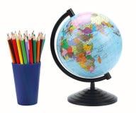 Fondo della scuola Globo con le matite colorate isolate su fondo bianco Fotografia Stock