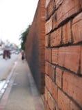 Fondo della sfuocatura della parete e della via di mattoni Fotografia Stock Libera da Diritti