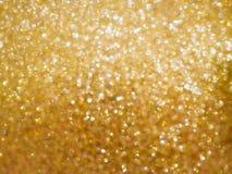 Fondo della sfuocatura della luce del bokeh di incandescenza dorata di Natale immagini stock