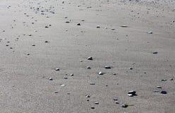 Fondo della spiaggia sabbiosa con le piccole pietre Fotografia Stock