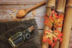 Fondo della stazione termale con bambù, sale da bagno, il petrolio di massaggio, le foglie di autunno e l'asciugamano Immagini Stock