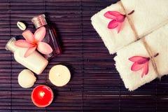 Fondo della stazione termale con le bottiglie dello sciampo, asciugamani bianchi, flusso tropicale Fotografia Stock