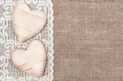 Fondo della tela da imballaggio con il panno di pizzo ed i cuori di legno Fotografie Stock