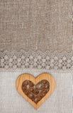 Fondo della tela da imballaggio con il panno di pizzo ed il cuore di legno Immagine Stock