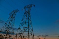 Fondo della torre ad alta tensione il tramonto nell'orizzonte Immagini Stock