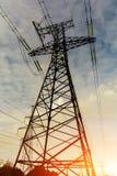 Fondo della torre ad alta tensione nel tramonto Immagini Stock