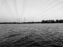 Fondo della vista del fiume con la linea incrocio di distribuzione di energia il fiume Fotografia Stock Libera da Diritti