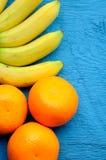 Fondo delle arance delle banane sul blu Fotografia Stock Libera da Diritti