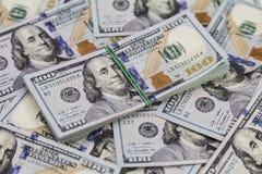 Fondo delle banconote in dollari e un pacco dei dollari sulla cima Fotografia Stock Libera da Diritti