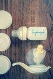 Fondo delle tiralatte e del biberon manuali con latte Fotografie Stock