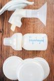 Fondo delle tiralatte e del biberon manuali con latte Fotografia Stock
