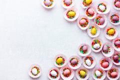 Fondo delle uova di Pasqua - mini uova del cioccolato in tazze della caramella con Fotografia Stock